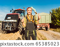 Farmer woman in front of agricultural machinery giving thumbs-up 65385023