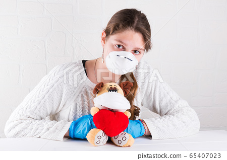 a girl wearing face mask is hugging a toy dog in medical mask holding a red heart 65407023