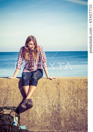 Man tourist backpacker sitting on grunge wall 65407710