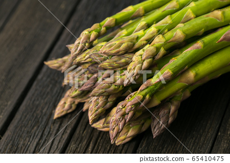 Bunch of fresh asparagus on wooden table 65410475