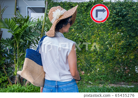 The female traveler looks at the traffic sign 65435276
