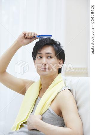 修飾他的頭髮的年輕男子的畫像 65439426