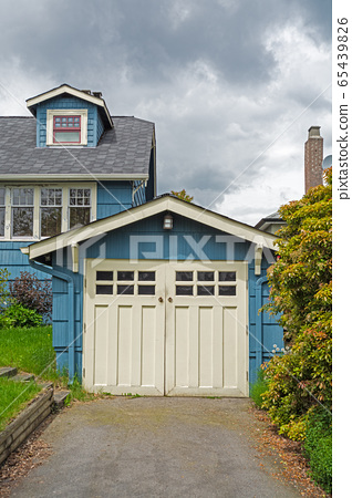 Detached single stall garage on front yard of residential house 65439826
