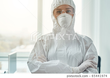 Young woman wearing protective suit and respirator 65441974