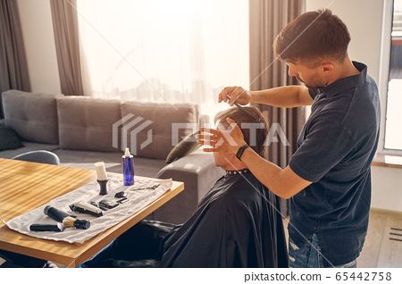 Man standing and cutting hair of his client 65442758