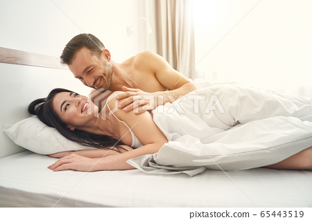 Happy newlyweds enjoying their morning in bed 65443519