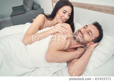 Happy married couple lying in a bedroom 65443571