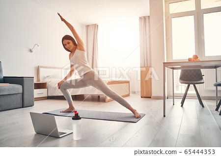 Attractive young female person doing stretching exercise 65444353