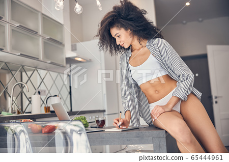 Girl with a diary sitting on the kitchen table 65444961