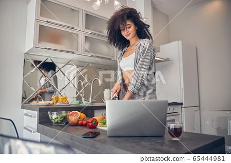 Beautiful dark-haired girl following an online recipe 65444981