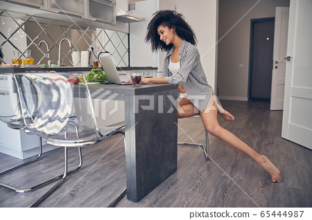 Smiling barefoot pretty woman working from home 65444987
