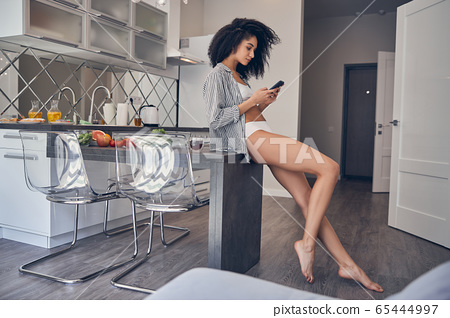 Relaxed dark-haired girl sitting in the kitchen 65444997