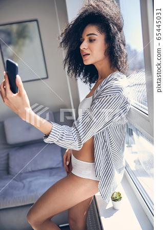 Modern pretty lady taking a selfie indoors 65445031