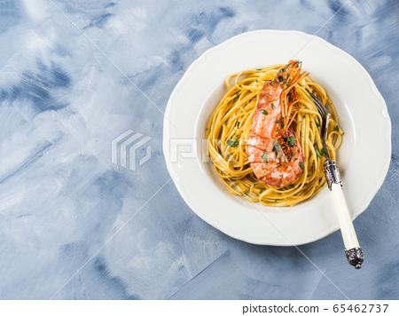 Linguine pasta with tiger prawn sauce in white dish 65462737