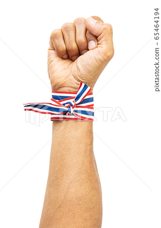 Raising up fist with Thai national color cloth tied around wrist on white background with clipping path 65464194