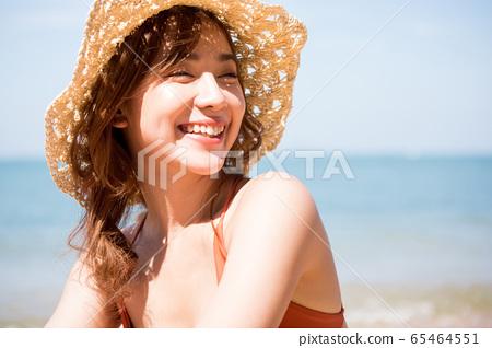 泳裝的一名婦女坐在海灘 65464551