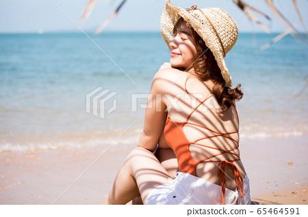 泳裝的一名婦女坐在海灘 65464591