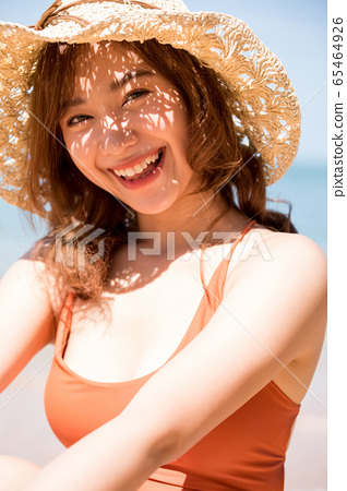 A woman in a swimsuit sitting on the beach 65464926