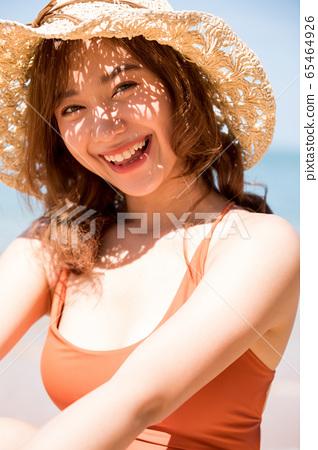 泳裝的一名婦女坐在海灘 65464926