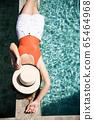 一个女人在游泳池旁放松的泳装 65464968