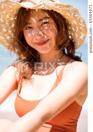 泳裝的一名婦女坐在海灘 65464971