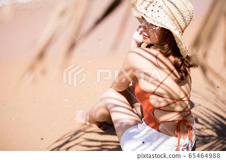 해변에 앉아 수영복 차림의 여성 65464988