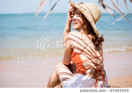 泳裝的一名婦女坐在海灘 65465008
