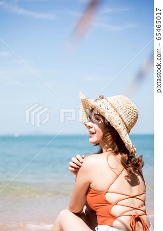 泳裝的一名婦女坐在海灘 65465017
