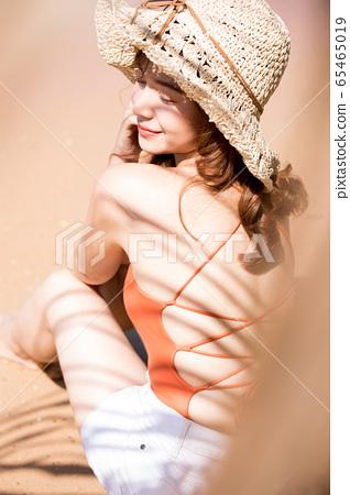 泳裝的一名婦女坐在海灘 65465019