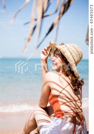 泳装的一名妇女坐在海滩 65465073
