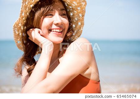 泳裝的一名婦女坐在海灘 65465074