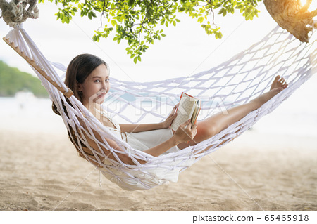 Asian Woman lying in a hammock on the beach 65465918