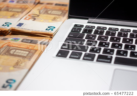 open laptop and stacks of money euro banknotes 65477222