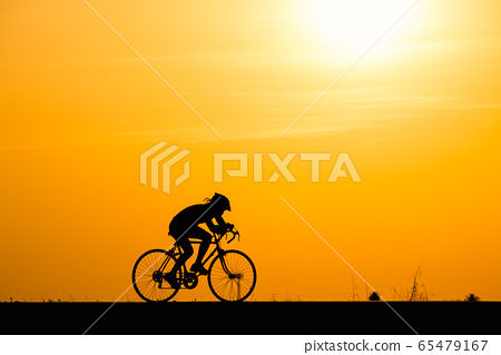 Silhouette woman cycling on sunset background 65479167