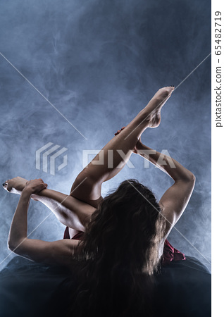 Concept of art, creativity and passion. Flexible woman on black background  65482719