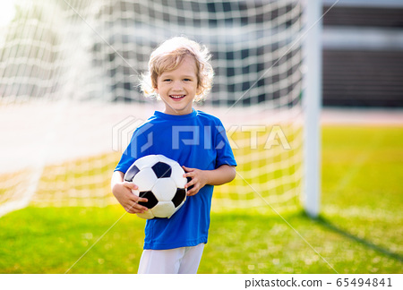 Kids play football. Child at soccer field. 65494841