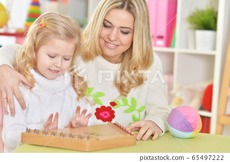 Portrait of mother with little daughter playing on musical instrument 65497222