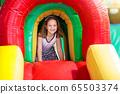 Child jumping on playground trampoline. Kids jump. 65503374