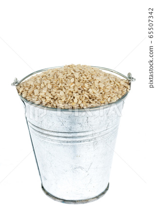 Full bucket of sesame seeds on a white background. 65507342
