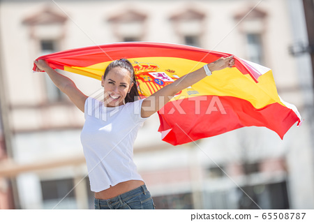 Beautiful girl holds a Spanish flag in her hands 65508787