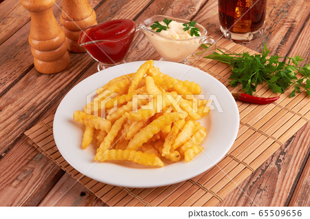 french fries on wooden table 65509656