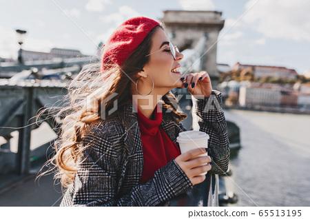 Carefree caucasian woman in red hat enjoying city 65513195