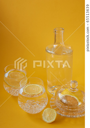 Refreshing water with lemon on a yellow background. Healthy lifestyle,thirst quenching. 65513639
