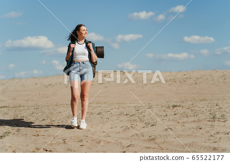 Woman with backpack hiking in desert. Traveling 65522177