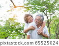 Senior woman piggy back senior man with love and happiness in park. Elderly asian couple have good health, smiley faces. Old couple always stay together. Grandmother, grandfather have long life 65525024
