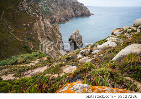 Cabo da Roca travel destination located in Sintra, Portugal. Hidden rocky rough beach surrounded by cliffs and Atlantic Ocean 65527226