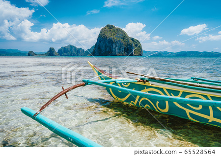 Holiday vacation vibes, tourism vivid colored boat on tropical sandy beach with island, blue sky and clouds in background 65528564