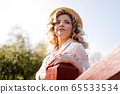Beautiful woman in summer dress and straw hat stands on birch bridge in the park 65533534