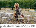 Young blond girl sitting at table in public park 65535391
