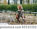 Young blond girl sitting at table in public park 65535392